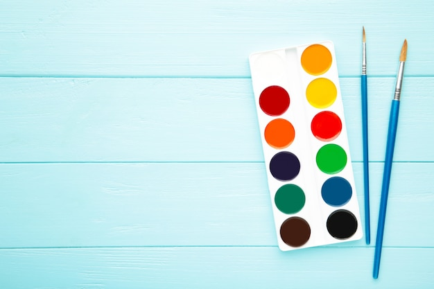 Aquarellfarben, die mit pinsel auf blauem hölzernem hintergrund eingestellt werden