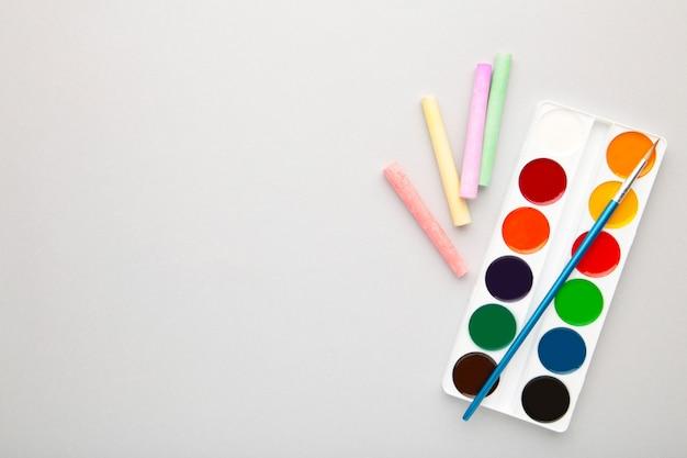 Aquarellfarben eingestellt mit pinseln und buntstiften zum zeichnen auf grauem hintergrund