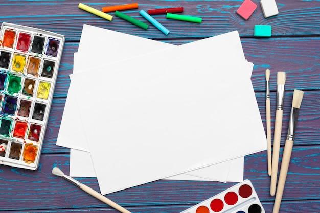 Aquarellfarben und leerer notizblock auf hölzernem schreibtisch