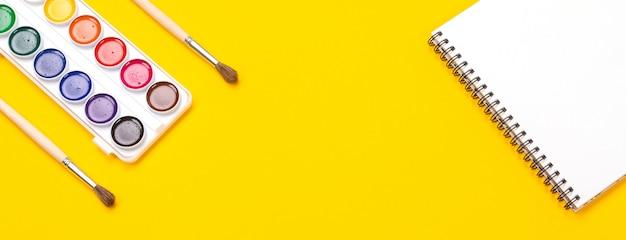 Aquarellfarben und -pinsel mit segeltuch für das malen mit copyspace auf gelbem hintergrund