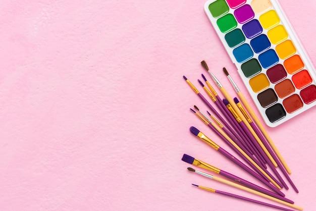 Aquarellfarben und pinsel zum zeichnen auf einem rosa