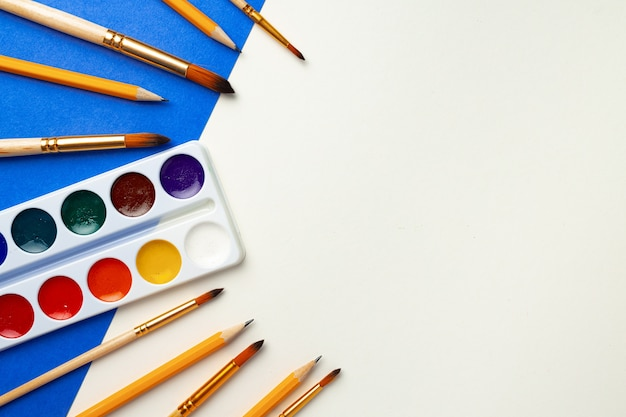 Aquarellfarbkasten und satz von pinseln auf blauem und weißem hintergrund draufsicht