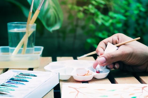 Aquarellmalerei, hobby- und glücklebensstil, abschluss herauf hand mit wasserfarbrohr