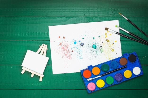 Aquarellmalereiausrüstung und beflecktes strukturiertes papier auf grünem hintergrund