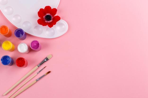 Aquarellpalette und -bürsten auf rosa hintergrund