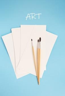 Aquarellpinsel unterschiedlicher größe liegen zusammen mit aquarellpapier auf blauem grund. zeichenunterricht. nahaufnahme, ansicht von oben. inschrift kunst.
