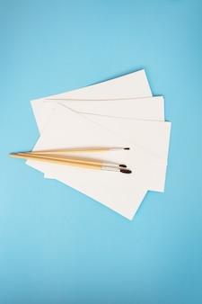 Aquarellpinsel unterschiedlicher größe liegen zusammen mit aquarellpapier auf blauem grund. zeichenunterricht. nahaufnahme, draufsicht.