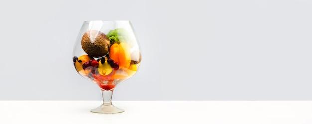 Aquarium mit gesundem essen, obst, gemüse und beeren (erdbeeren, erdbeere, himbeere, kokosnuss, brokkoli, pfeffer, orange, zitrone) saft saftig auf einer weißen wand