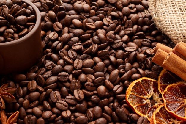 Arabica und robusta duftende kaffeebohnen sind auf sackleinen verstreut. lehmcup-kaffeebohnen-zimt