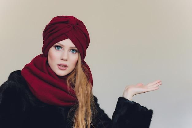 Arabische dame, die rote wollmütze trägt