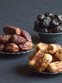 Arabische dattelfrüchte werden auf einem dunklen tisch ausgelegt