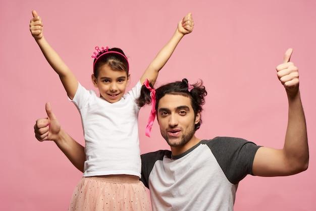 Arabische familie. vater und tochter. rosa hintergrund.