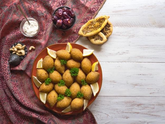 Arabische fleisch vorspeise kibbeh. traditionelles arabisches kibbeh mit lamm- und pinienkernenhintergrund