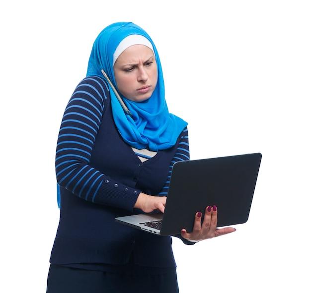 Arabische frau, die auf handy spricht und laptop verwendet