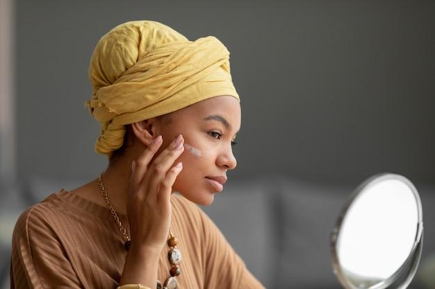 Arabische frau, die creme in ihrem gesicht aplying. schönheitsbehandlung