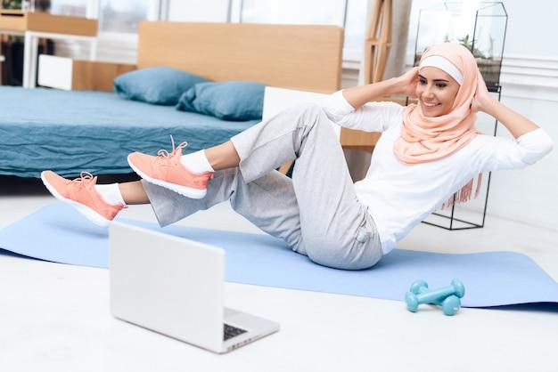 Arabische frau, die gymnastik im schlafzimmer tut