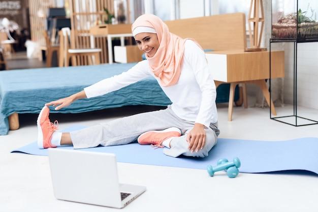 Arabische frau, die gymnastik im schlafzimmer tut.