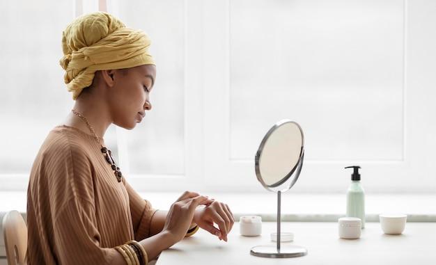 Arabische frau, die sahne in ihren händen aplying. schönheitsbehandlung