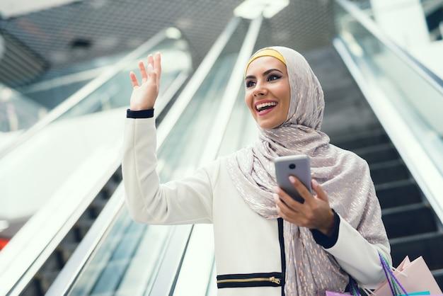 Arabische frau, die smartphone auf dem einkaufen verwendet.