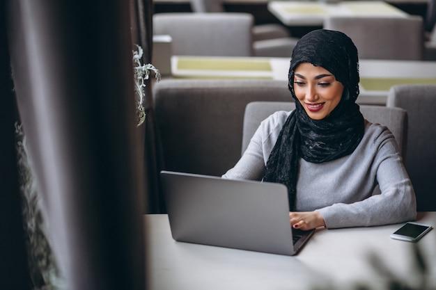 Arabische frau im hijab innerhalb eines cafés, das an laptop arbeitet