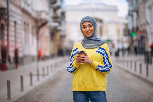 Arabische frau im hijab ouside in trinkendem kaffee der straße