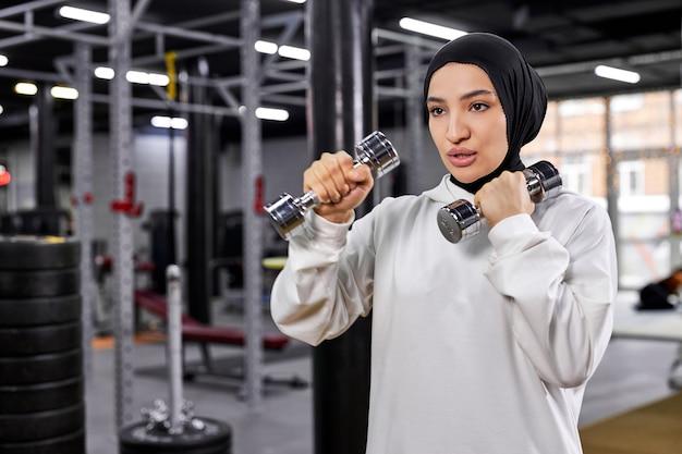 Arabische frau im weißen hijab, der mit hanteln im fitnessstudio trainiert, aktiven gesunden lebensstil genießt, sich auf training konzentriert, raum kopiert. sport, fitness, trainingskonzept