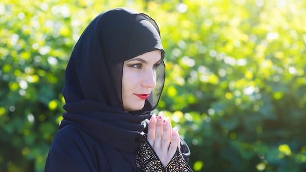 Arabische frau in schwarzer kleidung betet zu gott vor einem hintergrund grüne bäume.