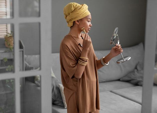 Arabische frau mit einem gesichtsmassagegerät. schönheitsbehandlung