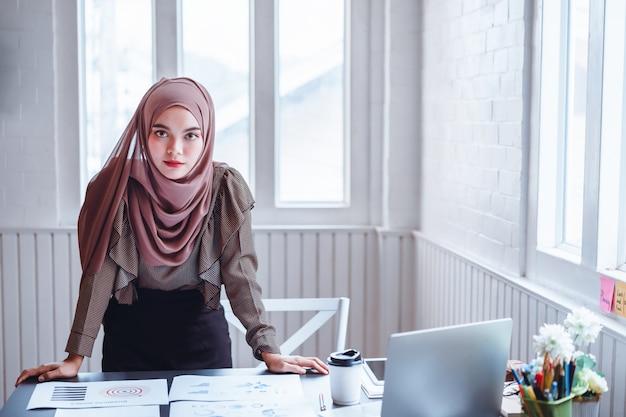 Arabische geschäftsfrau im braunen hijab am büroarbeitsplatz.