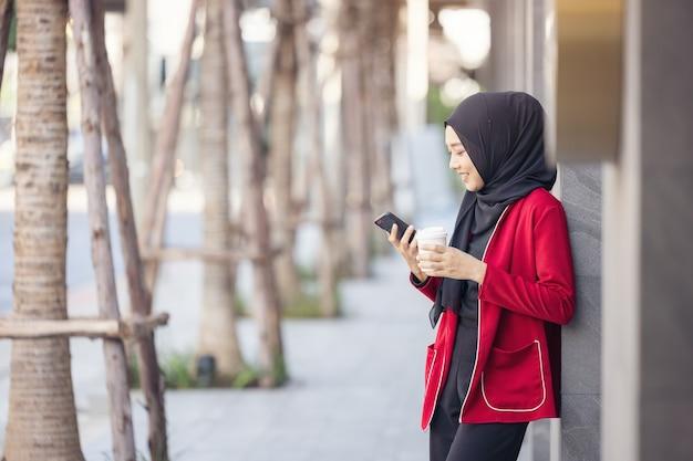 Arabische geschäftsfrauen im hijab halten einen kaffee auf der straße und halten ein handy