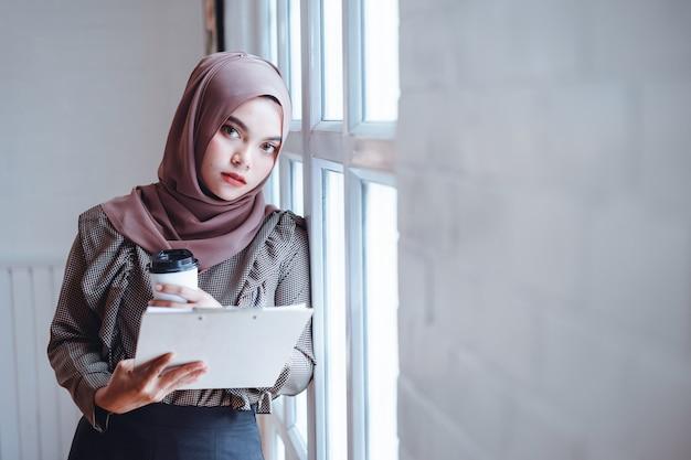 Arabische geschäftsfrauhand, die geschäftsunterlagen und eine papierkaffeetasse am büroarbeitsplatz verwahrt.