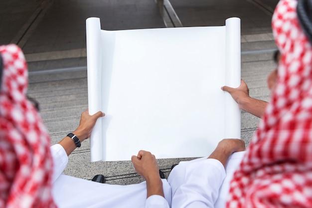 Arabische geschäftsmannhand, die leeres weißbuch hält.