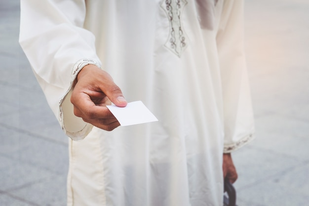 Arabische geschäftsmannhand, die visitenkarte zeigt