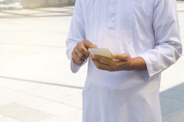 Arabische geschäftsmannmitteilung an einem handy in der stadt