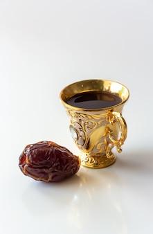 Arabische goldene luxusschale des schwarzen kaffees und des weißen hintergrundes der daten. ramadan-konzept.