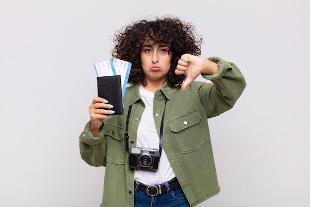Arabische hübsche frau mit einem flugzeug und bordkarten. reisekonzept