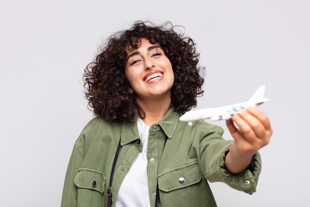 Arabische hübsche frau mit einem flugzeugmodell. traver-konzept