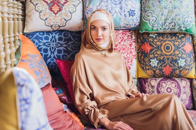 Arabische junge muslimische frau, die in einem café sitzt.