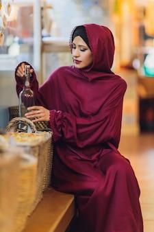 Arabische junge muslimische frau sitzt in einem café a