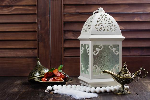 Arabische laterne, datteln, aladinlampe und rosenkranz auf holz