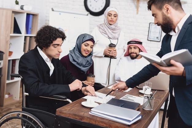Arabische leute besprechen die dokumente, die im büro sich treffen.