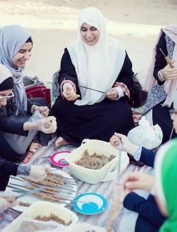 Arabische moslemische familie, die kebabfleisch für picknick zubereitet