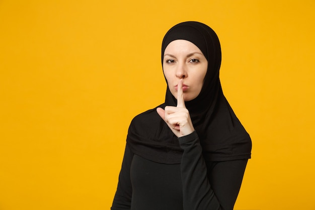 Arabische muslimische frau in hijab-schwarzer kleidung, die sagt, dass sie still sein soll, mit dem finger auf den lippen shhh-geste einzeln auf gelbem wandporträt menschen religiöses lifestyle-konzept.