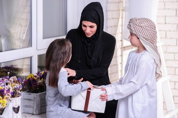 Arabische mutter, die ihren kindern ein geschenk gibt.