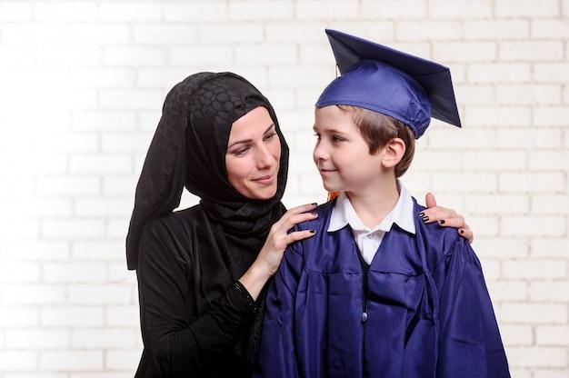 Arabische mutter posiert mit graduiertem sohn