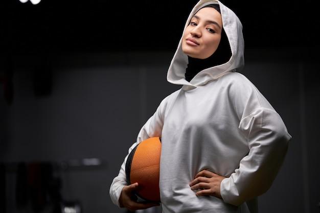 Arabische sportlerin mit ball in den händen, die bereit sind, basketball zu spielen, steht beim betrachten der kamera lächelnd, im weißen sportlichen hijab