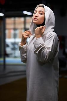 Arabische sportlerin steht posierend im fitnessstudio nach dem training, porträt der muslimischen dame im weißen hijab posierend, kamera betrachtend.