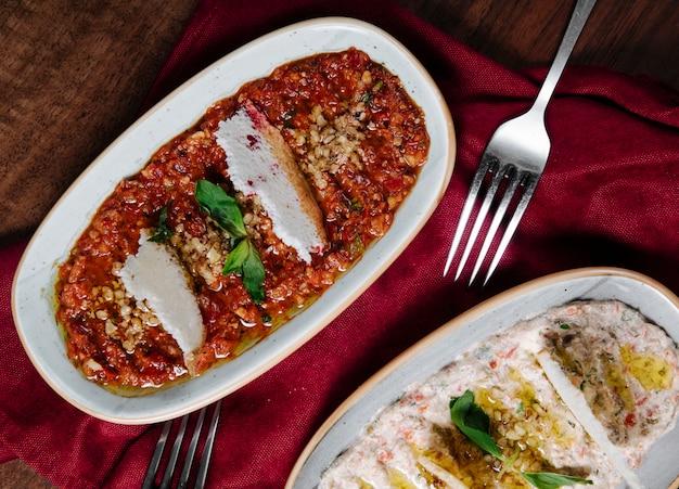 Arabischer apetizer humus mit joghurt und in tomatensauce mit kräutern.