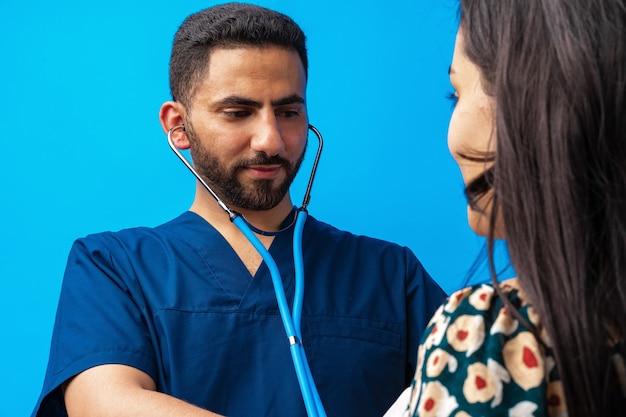 Arabischer arzt in blauer uniform, der mit dem stethoskop steht und dem herzschlag einer frau zuhört...