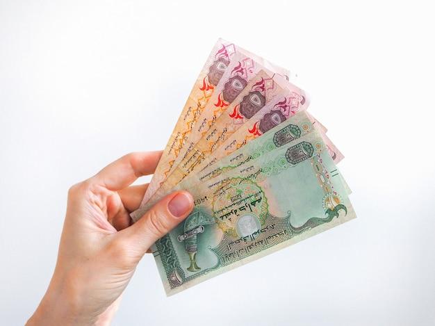Arabischer dirhams banknotenfächer von einer hand gehalten